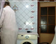 Hot hostess Lukerya in the kitchen in a dressing gown.